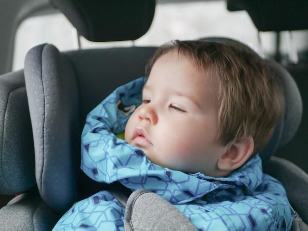 Śpiące Dziecko W Foteliku Samochodowym. Bezpieczeństwo Dziecka W Foteliku Samochodowym Podczas Snu. Premium Zdjęcia