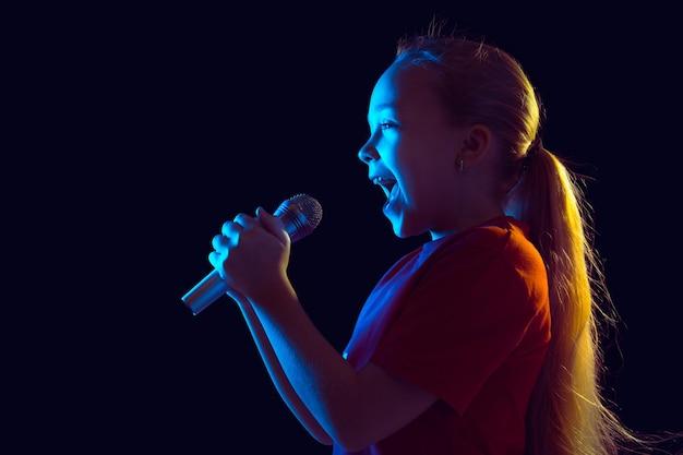 Śpiewam Radośnie. Portret Dziewczyny Kaukaski Na Ciemnym Tle Studio W świetle Neonu. Piękna Modelka Z Głośnikiem. Darmowe Zdjęcia