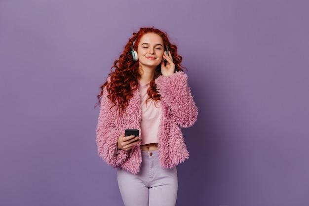 Spokojna Dziewczyna W Stylowym Różowo-białym Stroju Słuchająca Muzyki W Niebieskich Słuchawkach. Rudowłosa Kobieta Z Smartphone Na Bzu Przestrzeni. Darmowe Zdjęcia