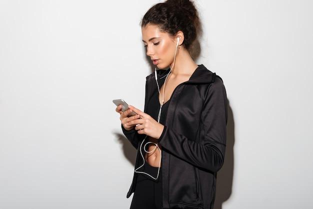 Spokojna Kędzierzawa Brunetki Sprawności Fizycznej Kobieta Słucha Muzykę I Używa Smartphone Darmowe Zdjęcia