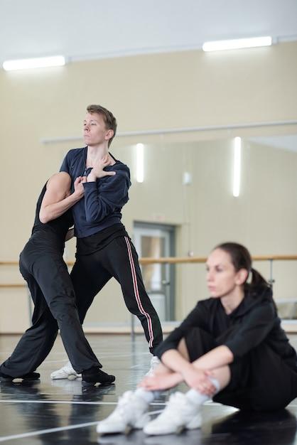 Spokojna Spokojna Kobieta W Czarnym Stroju Siedzi Na Podłodze W Studio Tańca, Podczas Gdy Młoda Para Tańczy W Pobliżu Premium Zdjęcia
