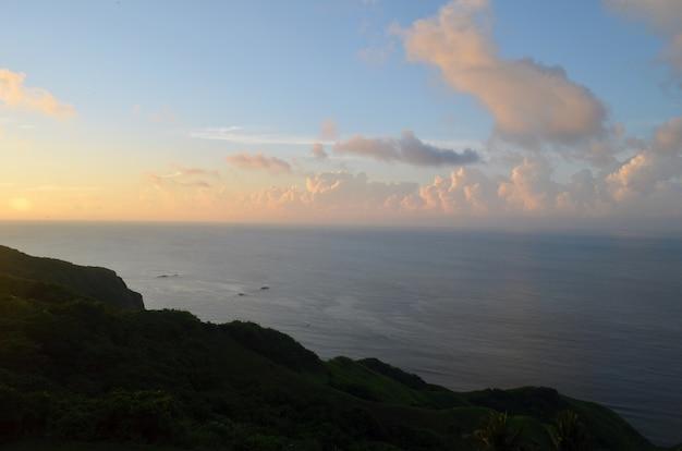 Spokojne Morze Otoczone Wzgórzami I Zielenią Podczas Zachodu Słońca Pod Błękitnym Niebem Darmowe Zdjęcia