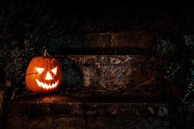 Spooky Halloween Pumpkin Lantern Na Betonowych Schodach W Ogrodzie W Nocy Premium Zdjęcia