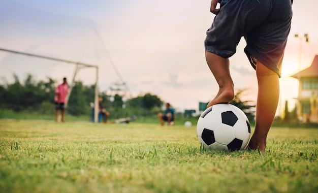 Sport akcji na świeżym powietrzu grupy dzieci bawiących się w piłkę nożną Premium Zdjęcia