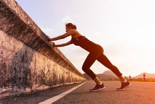 Sport Kobieta Biegacz Rozciąganie Mięśni Przed Uruchomieniem Na Długiej Drodze Premium Zdjęcia