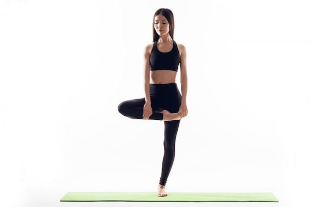 Sportowa dziewczyna stoi na jednej nodze. Premium Zdjęcia
