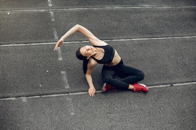 Sportowa dziewczyna trenuje na stadionie Darmowe Zdjęcia