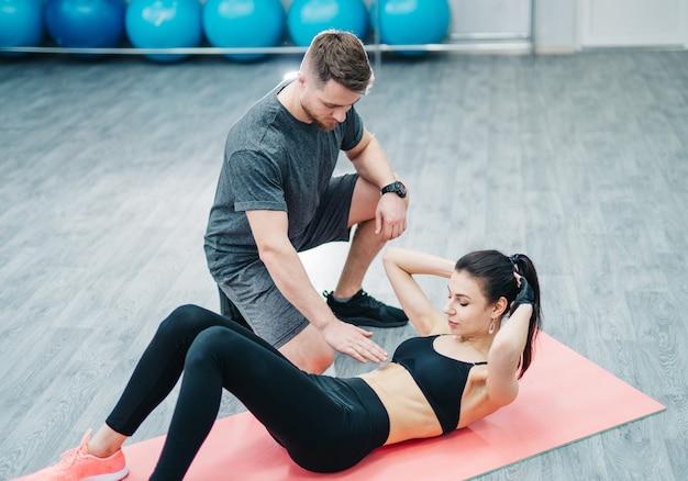 Sportowa Kobieta Robi Abs Na Podłodze I Męski Trener Trzyma Rękę Na Brzuchu Na Siłowni. Premium Zdjęcia