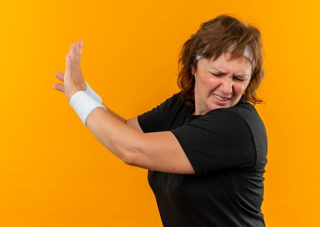Sportowa Kobieta W średnim Wieku W Czarnej Koszulce Z Pałąkiem Na Głowę, Czyniąc Gest Obrony Rękami Stojącymi Na Pomarańczowej ścianie Darmowe Zdjęcia