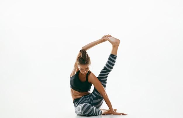 Sportowa Młoda Kobieta Robi Praktykę Jogi Na Białym Tle. Dopasuj Elastyczny Model ćwiczący Darmowe Zdjęcia