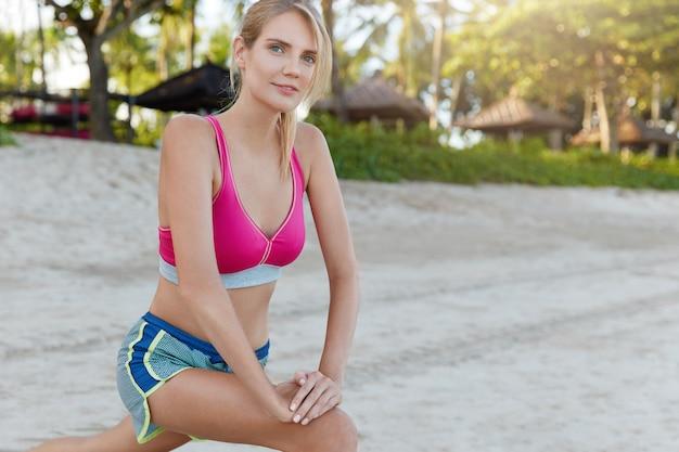 Sportowa Młoda Kobieta Ubrana W Jasny Strój Sportowy, ćwiczy Podczas Porannych Treningów Na Plaży, Pracuje Na Mięśniach Nóg, Uprawia Sport Na świeżym Powietrzu, Wykonuje ćwiczenia Rozciągające, Ma Smukłą Sylwetkę Darmowe Zdjęcia
