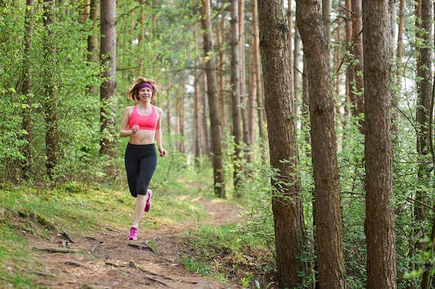 Sportowa młoda kobieta w różowych sneakers biega w wiosna lesie Premium Zdjęcia