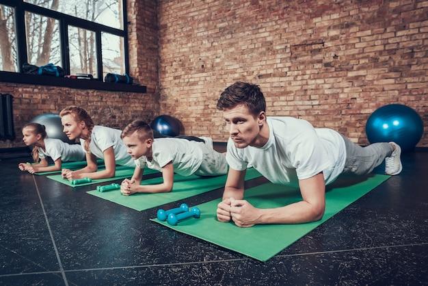 Sportowa rodzina ćwiczy deski w klubie fitness. Premium Zdjęcia