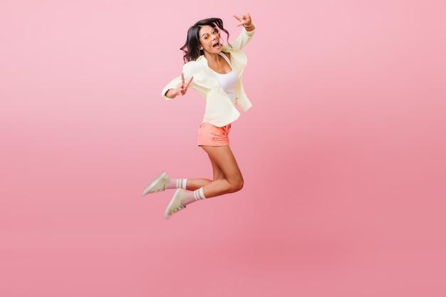 Sportowa Zmysłowa Latynoska Macha Rękami Podczas Skakania. Atrakcyjna Modelka W Ubranie Darmowe Zdjęcia