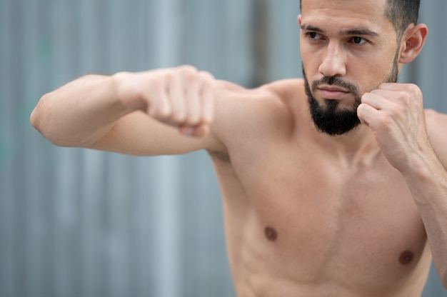 Sportowiec Prowadzi Walkę Z Cieniem. Bokser Trenuje Uderzenia Pięścią Na Ulicy Premium Zdjęcia