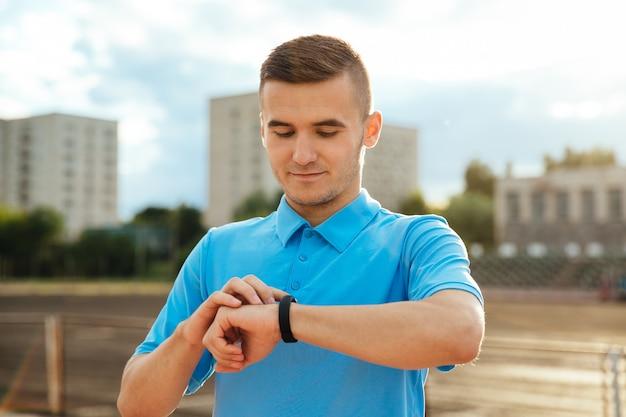 Sportowiec, Przystojny Mężczyzna Patrząc I Sprawdzanie Jego Zegarek Po Uruchomieniu Na Zewnątrz Darmowe Zdjęcia