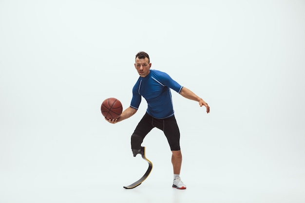 Sportowiec Z Niepełnosprawnościami Lub Po Amputacji Na Białym Tle Na Białej Przestrzeni Studio. Profesjonalny Koszykarz Z Treningiem Protezy Nogi I ćwiczeniami W Studio. Darmowe Zdjęcia