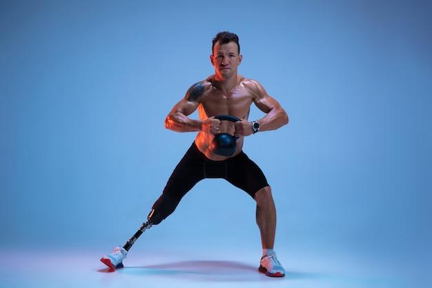 Sportowiec Z Niepełnosprawnościami Lub Po Amputacji Na Białym Tle Na Niebieskim Tle Studio. Profesjonalny Sportowiec Z Protezą Nogi Trenujący Z Ciężarami W Neonie. Darmowe Zdjęcia