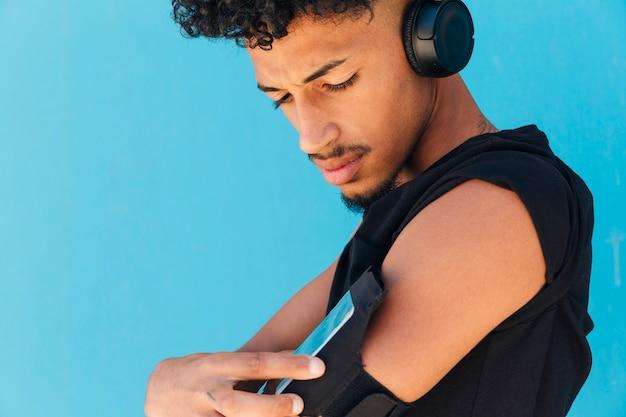 Sportowiec Ze Słuchawkami Za Pomocą Telefonu W Ramieniu Darmowe Zdjęcia