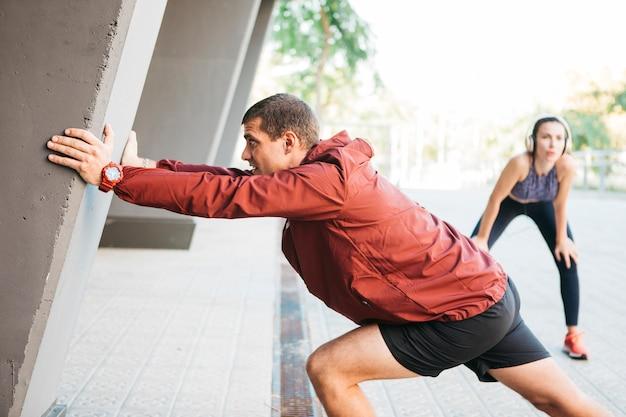Sportowy mężczyzna i kobieta rozciąganie w środowisku miejskim Darmowe Zdjęcia