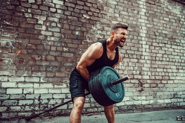 Sportowy Mężczyzna Pracujący Z Sztangą. Siła I Motywacja. ćwiczenia Na Mięśnie Pleców Premium Zdjęcia