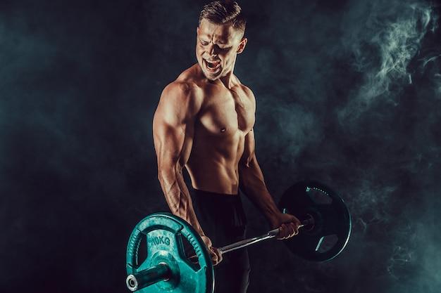 Sportowy Mężczyzna Robi ćwiczeniom Z Dumbbells Przy Bicepsami. Zdjęcie Silnego Mężczyzny Z Nagą Półpostacią Na Ciemnej ścianie. Siła I Motywacja. Premium Zdjęcia