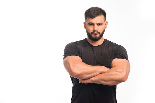 Sportowy Mężczyzna W Czarnej Koszuli, Zaciskając Mięśnie Ramion. Darmowe Zdjęcia