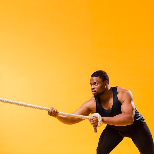 Sportowy Mężczyzna W Gym Stroju Ciągnięcia Arkanie Z Kopii Przestrzenią Darmowe Zdjęcia