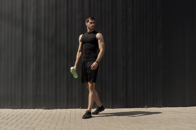 Sportowy Nowożytny Młody Człowiek Pozuje Na Szarej Kruszcowej ścianie Darmowe Zdjęcia