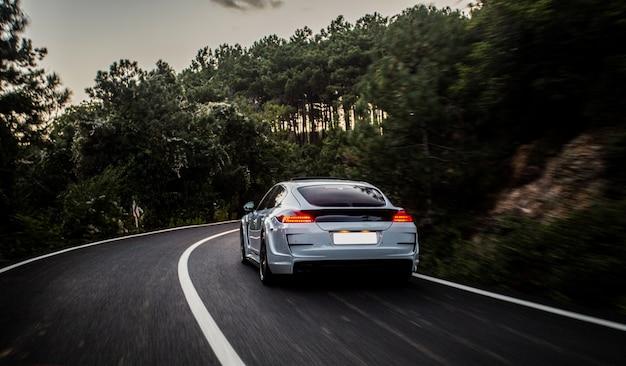 Sportowy Samochód Z Czarno-białym Autotuningiem Jadącym Do Lasu. Darmowe Zdjęcia