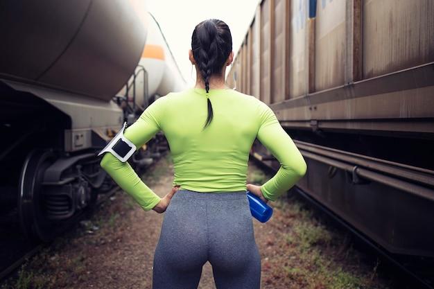 Sportsmenka Z Umięśnionym Ciałem Przygotowuje Się Do Biegania Między Pociągami Na Stacji Darmowe Zdjęcia