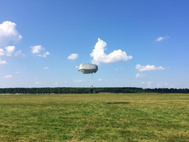 Sporty ekstremalne - spadochroniarz ląduje na ziemi Premium Zdjęcia