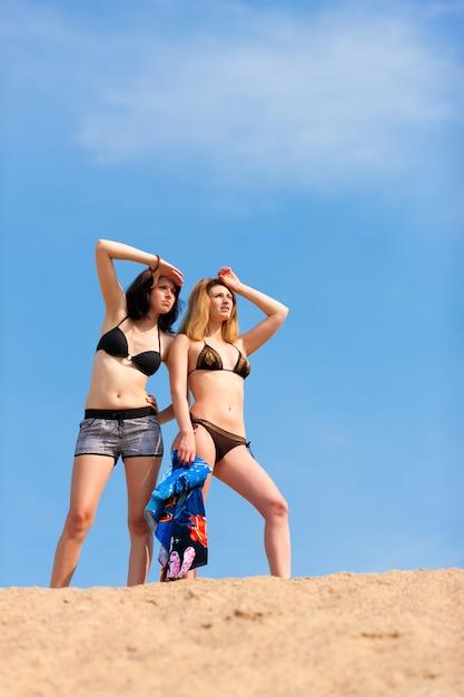 Sporty kobiety stoi w piasku patrzeje daleko od w odległości Premium Zdjęcia