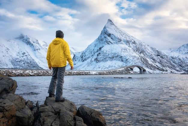 Sporty Mężczyzna W żółtej Kurtki Pozyci Na Kamieniu Na Seacoast Przeciw śnieżnym Górom I Chmurnemu Niebu Przy Zmierzchem W Zimie Premium Zdjęcia