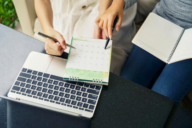Spotkanie w zespole, kobiety rozmawiają z agendą planowania i harmonogramem z wykorzystaniem wydarzenia w kalendarzu Premium Zdjęcia