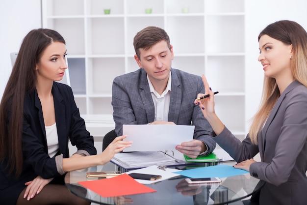Spotkanie z agentem w biurze, kupno wynajmu mieszkania lub domu, kupujących nieruchomości gotowych do zawarcia umowy, para rodzinna podająca sobie nieruchomości po podpisaniu dokumentów do zakupu nieruchomości Premium Zdjęcia