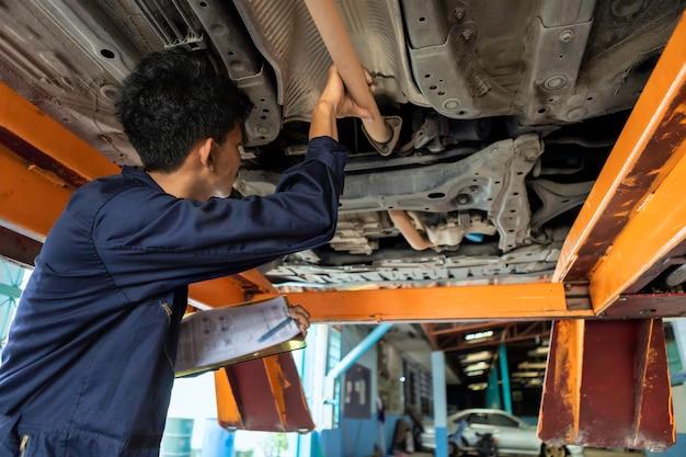 Sprawdź Listę. Mężczyzna Mechanik Naprawia Silnik Na Podnośniku Samochodowym. Za Pomocą Narzędzi Do Naprawy Samochodu W Garażu. Koncepcja Samochodu Serwisowego. Premium Zdjęcia