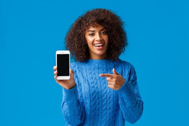 Sprawdź To. Szczęśliwa Charyzmatyczna Afroamerykańska Kobieta Z Afro Fryzurą, Trzyma Smartfon, Pokazuje Ekran Telefonu Komórkowego, Wskazuje Wyświetlacz Jako Promujący Aplikację, Aplikację Na Zakupy Lub Grę Premium Zdjęcia