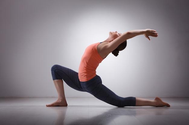 Sprawna Kobieta Yogini ćwiczy Asanę Jogi Anjaneyasana Premium Zdjęcia