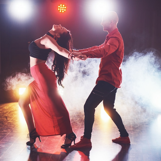 Sprawni Tancerze Występujący W Ciemnym Pokoju Pod Koncertowym światłem I Dymem. Zmysłowa Para Wykonująca Artystyczny I Emocjonalny Taniec Współczesny Darmowe Zdjęcia