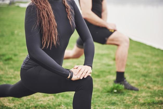 Sprawności Fizycznej Para Rozciąga Outdoors W Parku Blisko Wody. Młody Brodaty Mężczyzna I Kobieta Razem ćwiczenia Rano Darmowe Zdjęcia