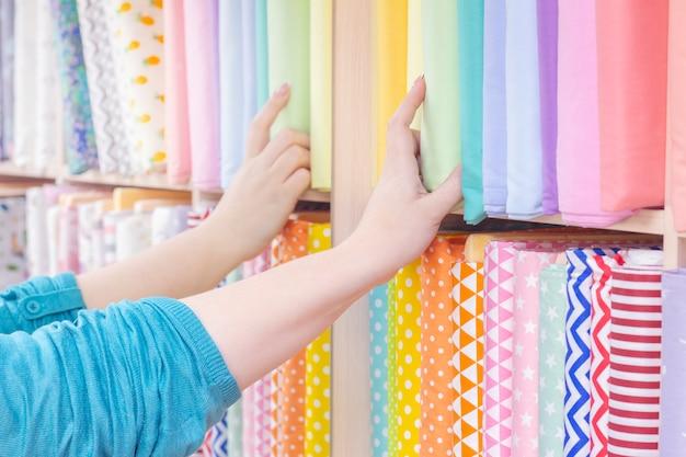 Sprzedawca I Kupujący Wybierają Materiał W Sklepie. Półki Z Tkanin Bawełnianych, Kolorowe Pastelowe Kolory. Premium Zdjęcia