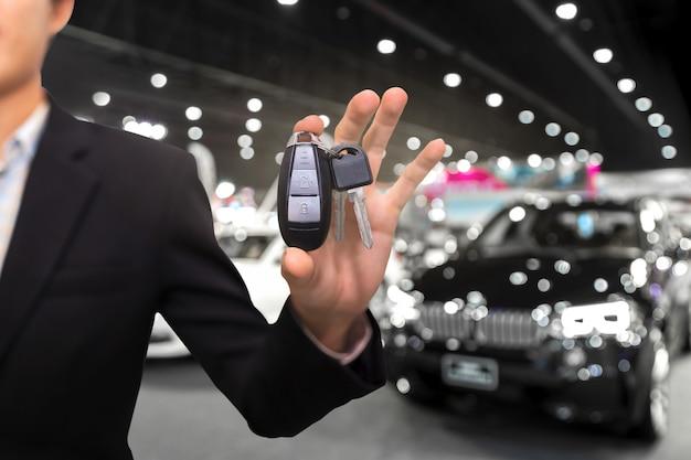 Sprzedawca lub sprzedawca oferujący klucze do nowego właściciela w salonie sprzedaży, koncepcji zakupu lub wynajmu. Premium Zdjęcia