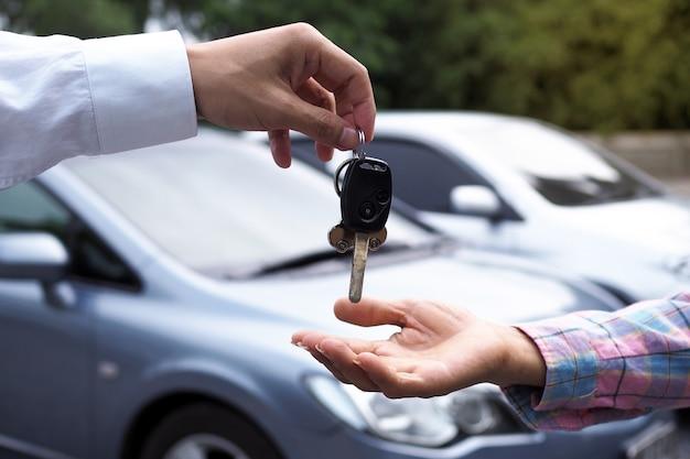 Sprzedawca samochodów i klucz do nowego właściciela. Premium Zdjęcia