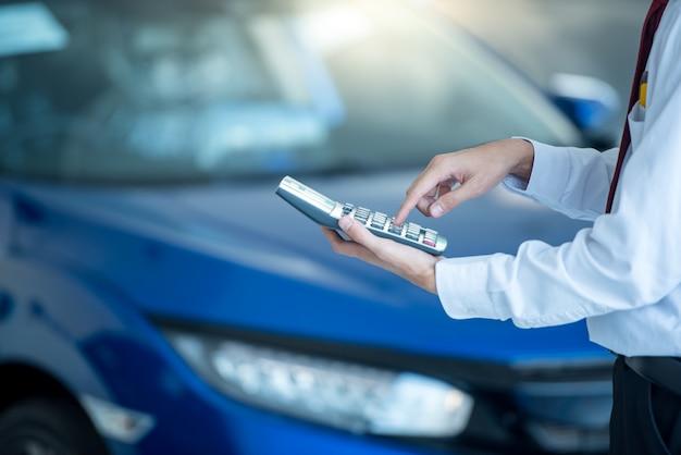 Sprzedawca samochodów naciskając kalkulator dla finansów przedsiębiorstw w salonie samochodowym nowy niebieski samochód Premium Zdjęcia