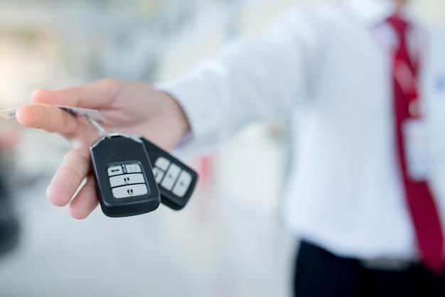 Sprzedawca samochodów przekazuje nowe kluczyki do samochodu Premium Zdjęcia