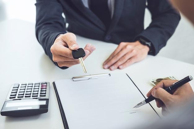 Sprzedawca wysyła klucz do klienta po podpisaniu przez człowieka umowy o podpisaniu dokumentu samochodowego Premium Zdjęcia