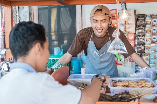 Sprzedawca Z Angkringa Uśmiecha Się, Obsługując Klientów Przy Stoisku Z Wózkami Premium Zdjęcia