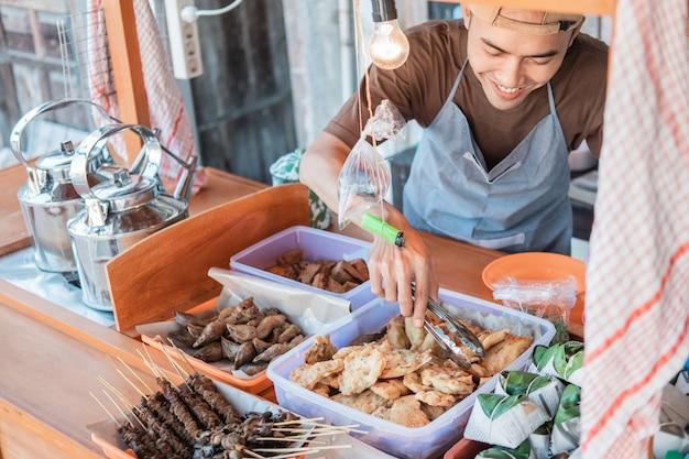 Sprzedawca Z Wózkami Uśmiechnął Się, Trzymając Szczypce Z Jedzeniem, żeby Posprzątać Ekspozycje Z Jedzeniem Na Straganie Premium Zdjęcia