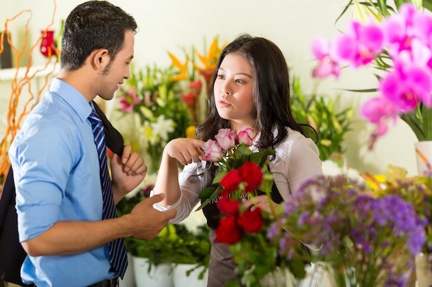 Sprzedawczyni i klient w kwiaciarni Premium Zdjęcia
